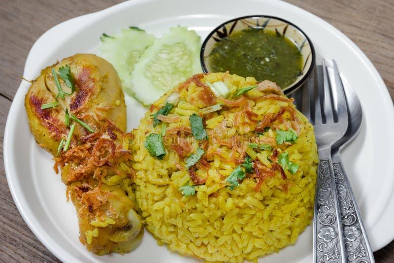 Chicken Biryani with cooked turmeric jasmine on wood background.  royalty free stock photography