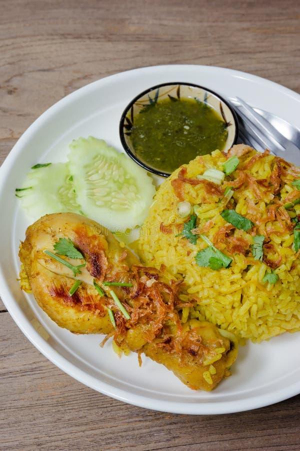 Chicken Biryani with cooked turmeric jasmine on wood background.  stock photo