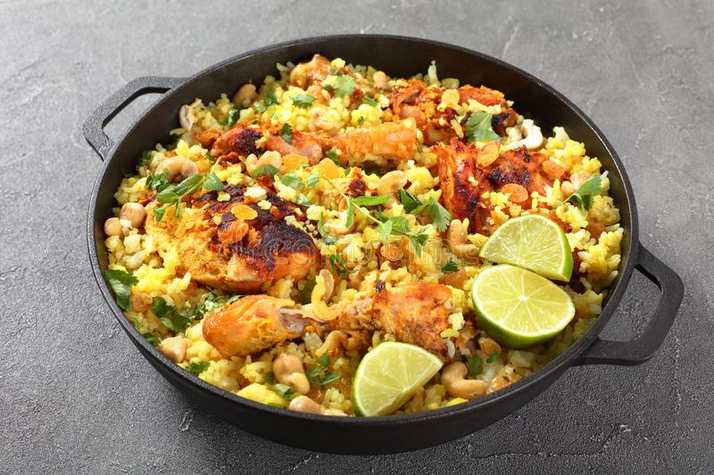 Chicken biryani, indian cuisine, top view. Chicken biryani - pieces of chicken marinated in yogurt sauce with spices, shredded ginger, fried onion rings, fresh royalty free stock photos