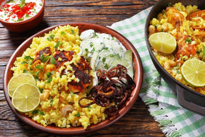 Chicken biryani, indian cuisine, top view. Portion of delicious chicken biryani or indian spicy chicken pilau served on clay plate with cucumber yogurt raita stock photography