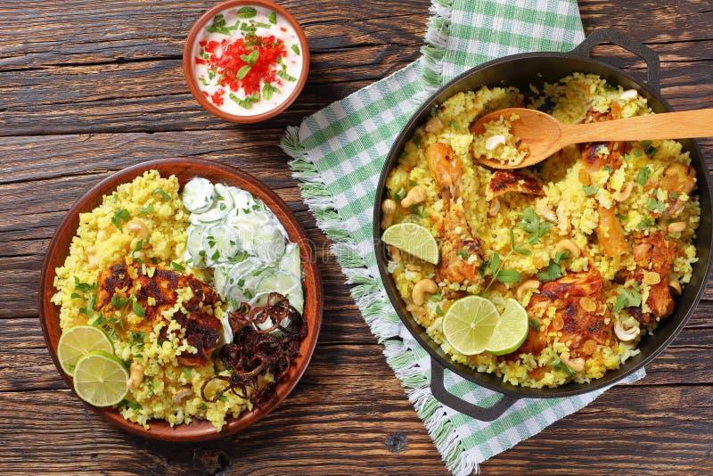 Chicken biryani or indian spicy chicken pilau. Delicious chicken biryani or indian spicy chicken pilau served on clay plate with cucumber yogurt raita,, view stock photography