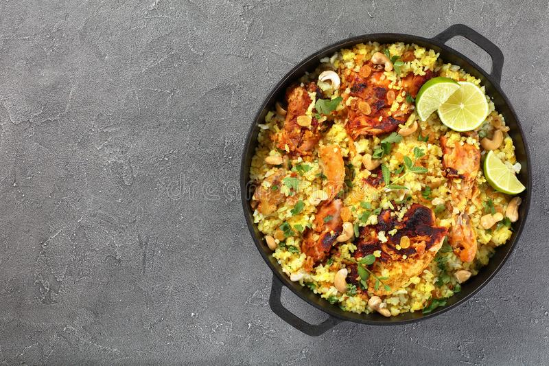 Chicken biryani n cast iron pan. Chicken biryani - pieces of chicken marinated in yogurt sauce with spices, shredded ginger, fried onion rings, fresh coriander stock image