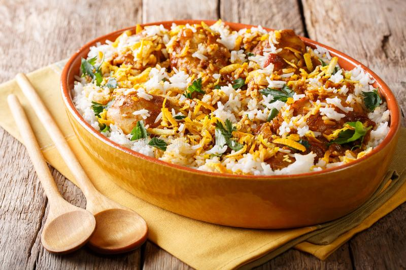 Chicken biryani with spicy spices, orange peel and cilantro close-up in a bowl. horizontal. Chicken biryani with spicy spices, orange peel and cilantro close-up royalty free stock photos
