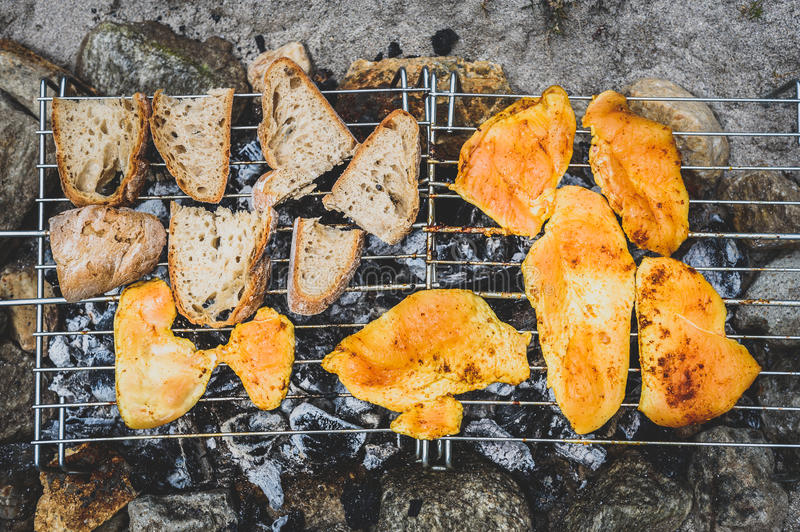 Chicken and bread on homemade improvised BBQ barbecue grill. royalty free stock image