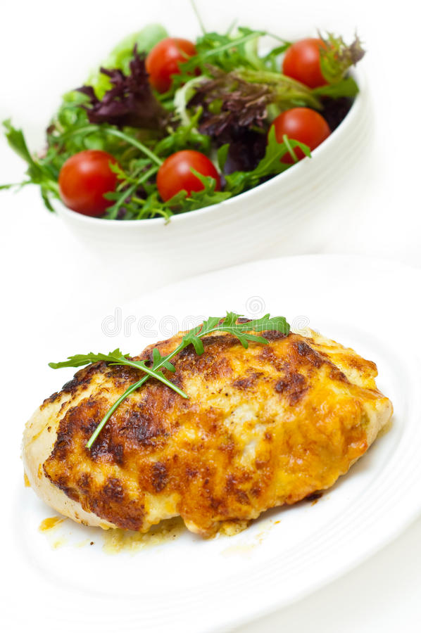 Chicken breast baked in cheese. And salad against white royalty free stock image