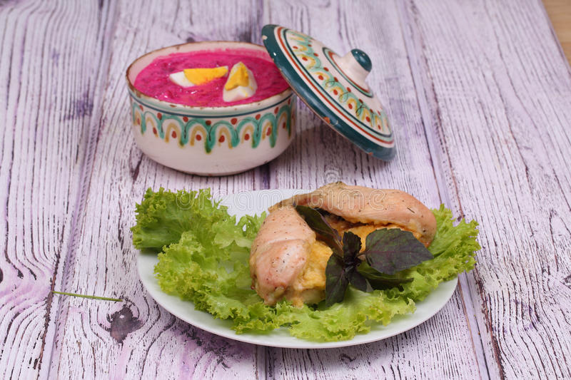 Chicken breast baked with cheese, a beetroot soup and greens. Chicken breast baked with cheese, fresh greens and a beetroot soup in a soup tureen royalty free stock image