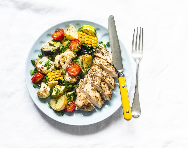 Chicken breast baked with potatoes, cauliflower, corn, eggplant, zucchini, cherry tomatoes on a light background, top view. stock photo