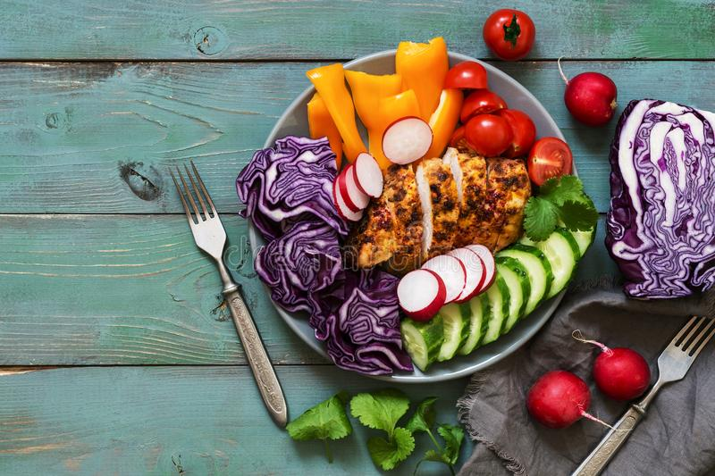 Chicken breast baked with spices is served with fresh vegetables, red cabbage, radish, cucumbers, sweet peppers, tomatoes on a gre royalty free stock photos