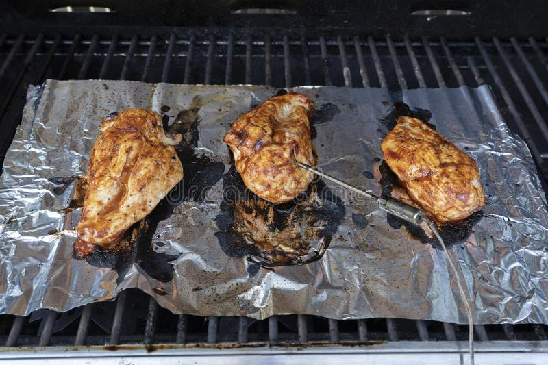 Chicken Breast Barbecuing On The Grill royalty free stock photos