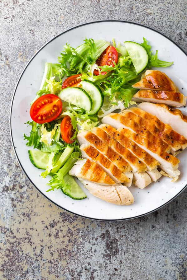 Chicken breast or fillet, poultry meat grilled and fresh vegetable salad of tomato, cucumber and lettuce royalty free stock photo