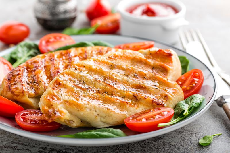 Chicken breast or fillet, poultry meat grilled and fresh vegetable salad of tomato and spinach stock photos