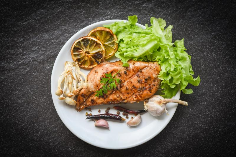 Chicken breast grilled with garlic chilli herbs and spices and fresh vegetables on plate top view - Roast BBQ chicken breast steak stock photos