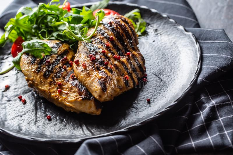 Chicken breast grilled with spices peper salt tomatoes and arugula stock photos