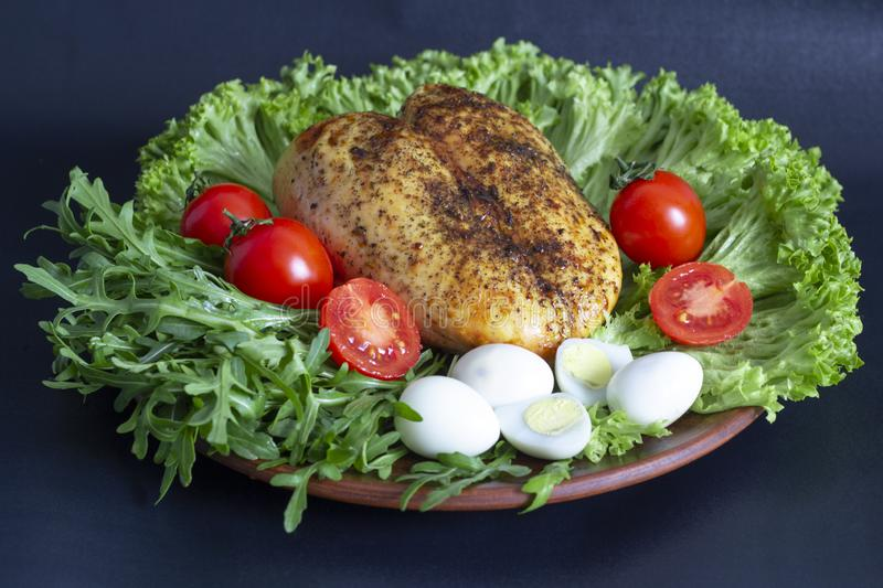 chicken breast on lettuce leaves with tomatoes and quail eggs royalty free stock image