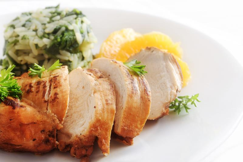 Chicken breast with orange fillets and spinach rice on a white plate, close up, copy space, stock photos