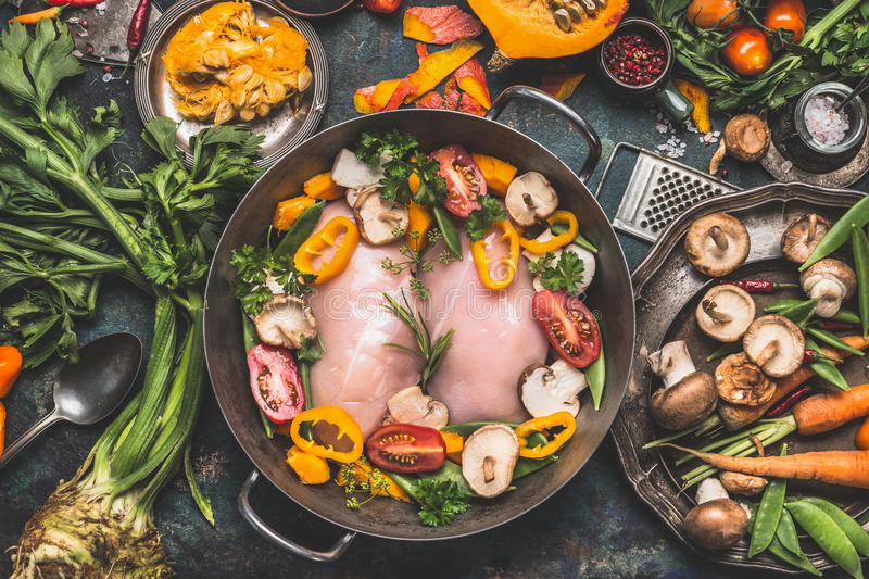 Chicken breast with Pumpkin and organic vegetables ingredients from garden, cooking preparation on dark rustic kitchen table, top royalty free stock photography