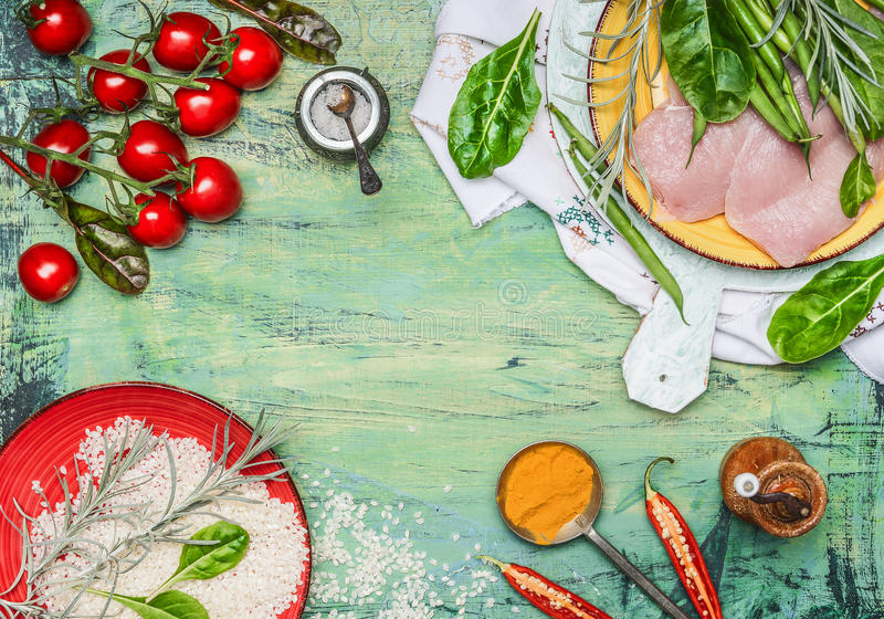 Chicken breast with rice, fresh delicious vegetables and ingredients for cooking on rustic wooden background, top view, frame royalty free stock photography