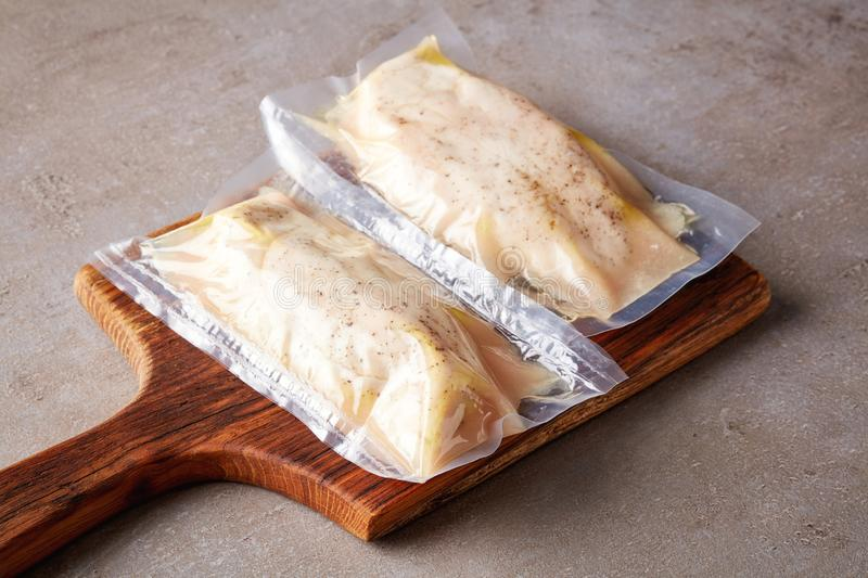 Chicken breast vacuum sealed on stone table. Chicken breast vacuum sealed ready for sous vide cooking stock photography