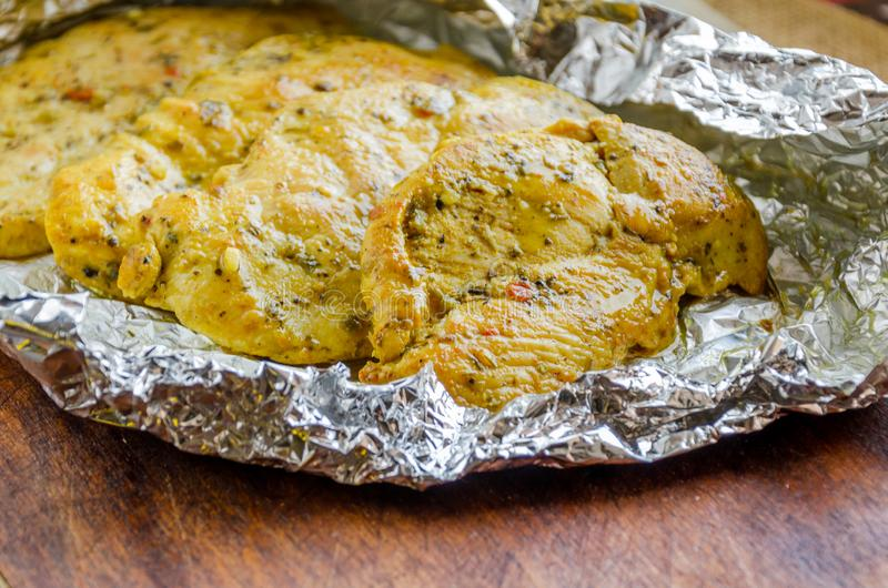 Chicken breasts baked with seasoning in foil stock photography