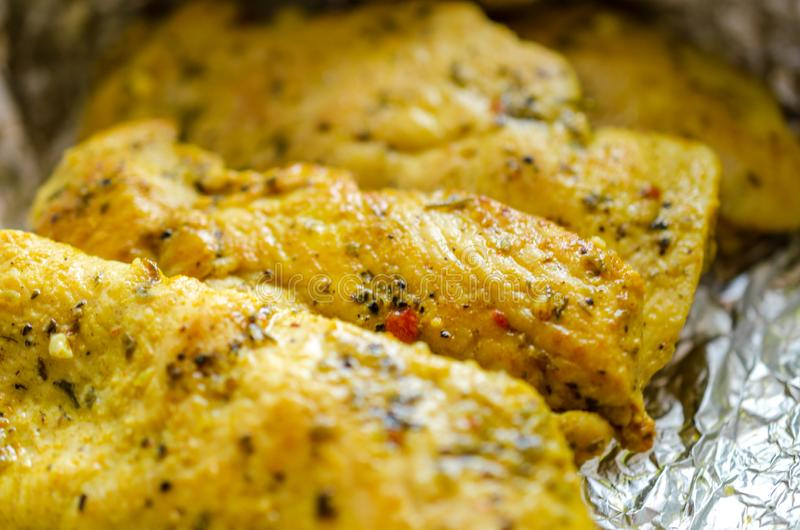 Chicken breasts baked with seasoning in foil stock images