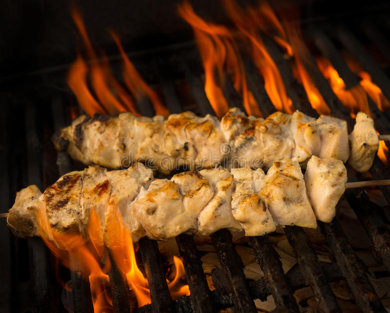 Chicken brochette on grill. Chicken brochette cooking on a barbecue grill with flame and fire. Shallow depth of field royalty free stock images