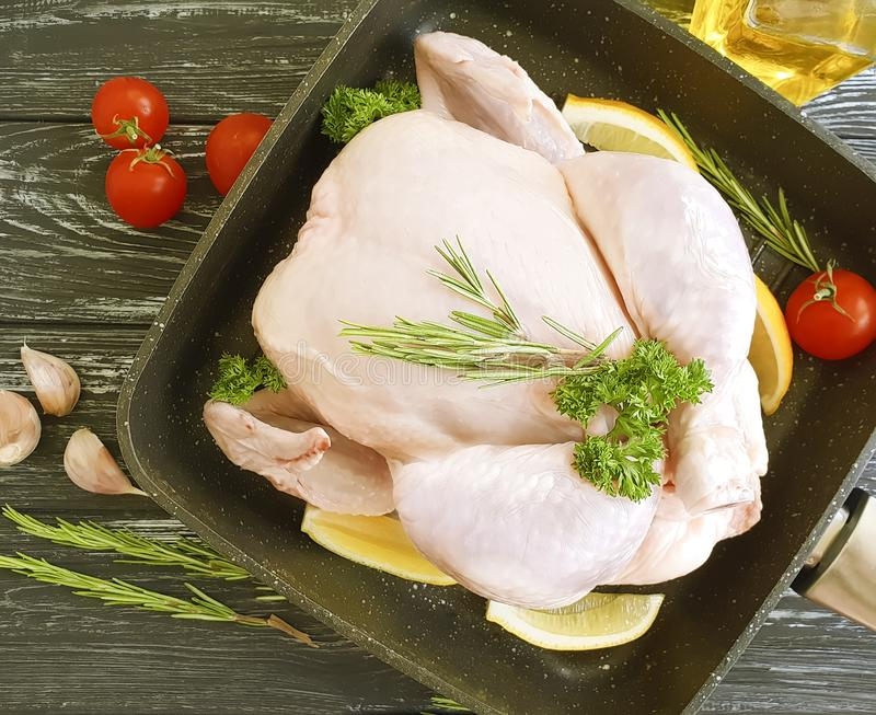 Chicken broiler whole cuisine dinner gourmet diet cuisine ingredient a frying pan on a white wooden background, tomato, lemon. Chicken broiler natural raw fresh stock photography
