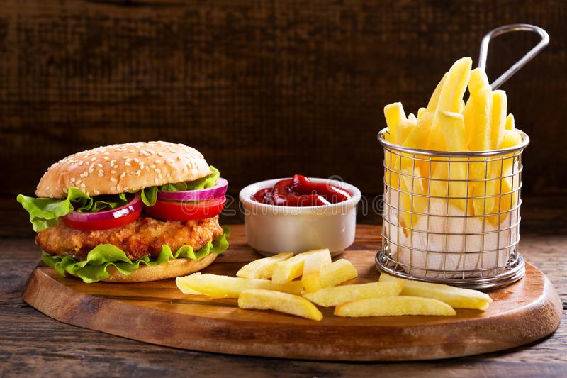 Chicken burger with french fries. On wooden board royalty free stock image