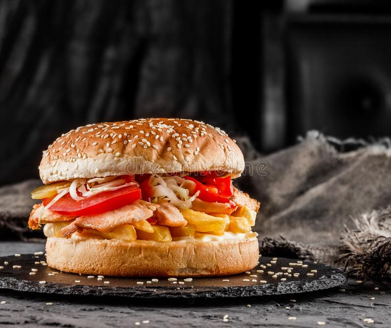 Chicken burger with tomatoes, french fries and sauce on black slate over dark background. Unhealthy food. Chicken burger with tomatoes, french fries and sauce royalty free stock photos