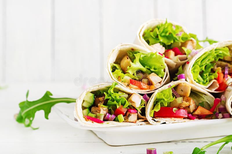 Chicken burrito. Healthy lunch. Mexican street food fajita tortilla wraps. With grilled chicken fillet and fresh vegetables royalty free stock photo