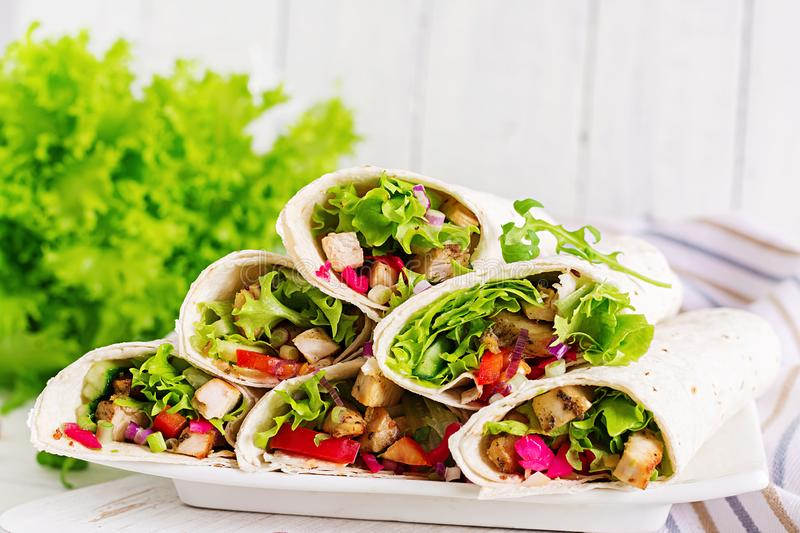 Chicken burrito. Healthy lunch. Mexican street food fajita tortilla wraps. With grilled chicken fillet and fresh vegetables stock image