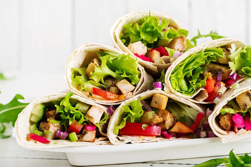 Chicken burrito. Healthy lunch. Mexican street food fajita tortilla wraps. With grilled chicken fillet and fresh vegetables royalty free stock photography