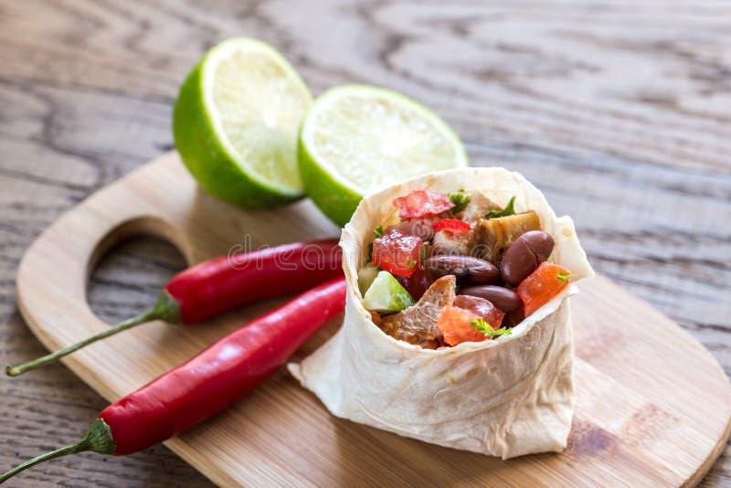 Chicken burrito. Portion of chicken burrito on the wooden board stock photography