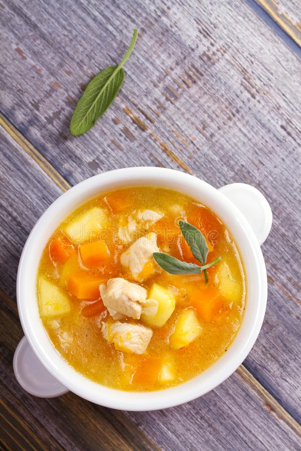 Chicken, butternut, apple ginger and sage stew. Pumpkin and chicken breast soup. View from above, top shot, vertical royalty free stock image