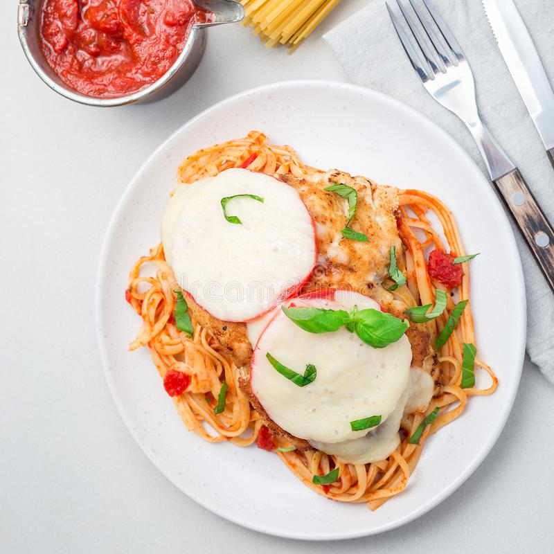 Chicken caprese with tomato and mozzarella cheese, served with linguine, tomato pasta sauce and basil, square, top view stock image