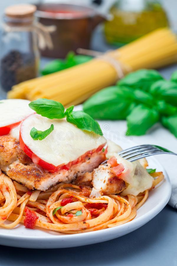 Chicken caprese with tomato and mozzarella cheese, served with linguine, tomato sauce and basil, vertical stock photo