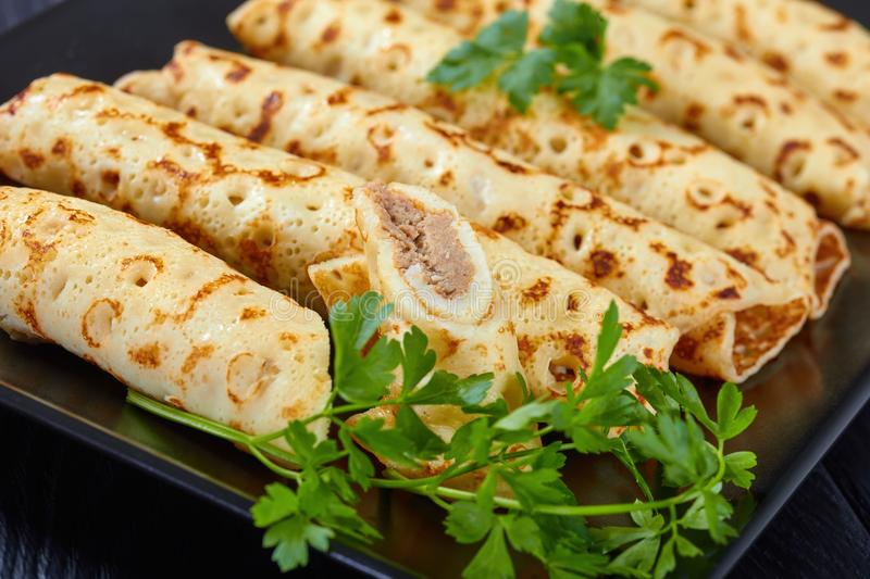 Chicken cheese pate stuffed crepes, close-up. Savory Homemade chicken pate stuffed crepes on a black plate with fresh parsley leaves, view from above, close-up royalty free stock image