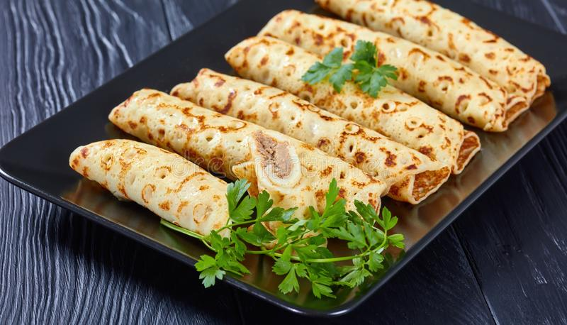 Chicken cheese pate stuffed crepes, top view. Savory Homemade chicken cheese pate stuffed crepes on a black plate with fresh parsley leaves, view from above royalty free stock images