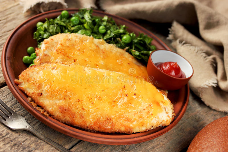 Chicken cheese schnitzel with green salad and tomato sauce royalty free stock photos