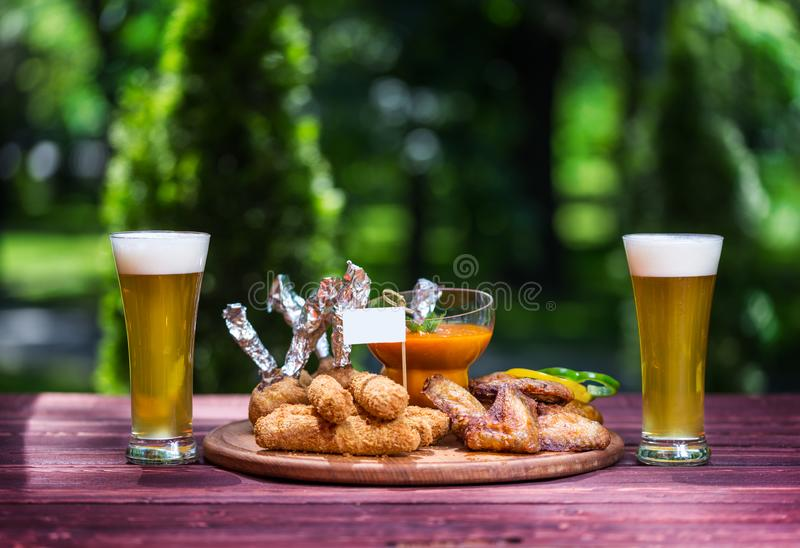 Chicken and Cheese Set for beer and two glasses of beer. Chicken wings, cheese sticks and cheese balls with bright royalty free stock photography