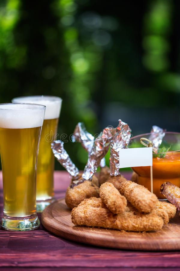Chicken and Cheese Set for beer and two glasses of beer. Chicken wings, cheese sticks and cheese balls with bright royalty free stock image