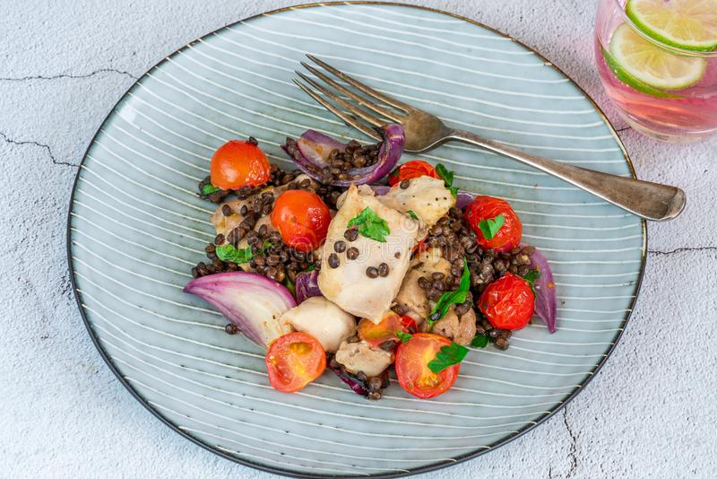Chicken, puy lentils and cherry tomatoes bake. Chicken and cherry tomatoes bake with puy lentils - high angle view royalty free stock images