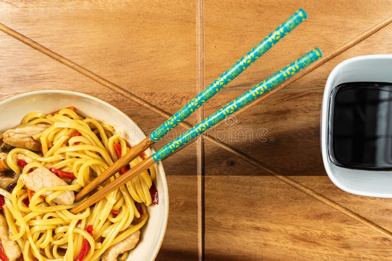 Chicken chow mein and chopsticks on wooden table stock images