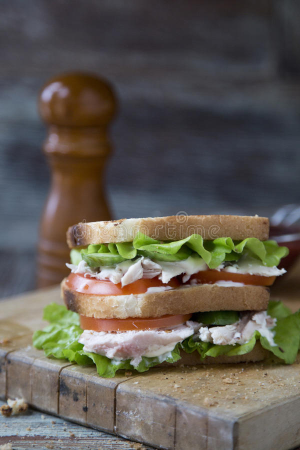 Chicken Club Sandwich with Lettuce and Tomato. On old wooden table royalty free stock image