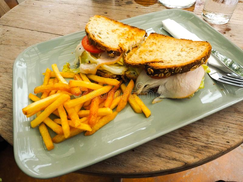 Chicken club sandwich on a white plate with spicy french fries. Very Shallow depth of field.  royalty free stock photo