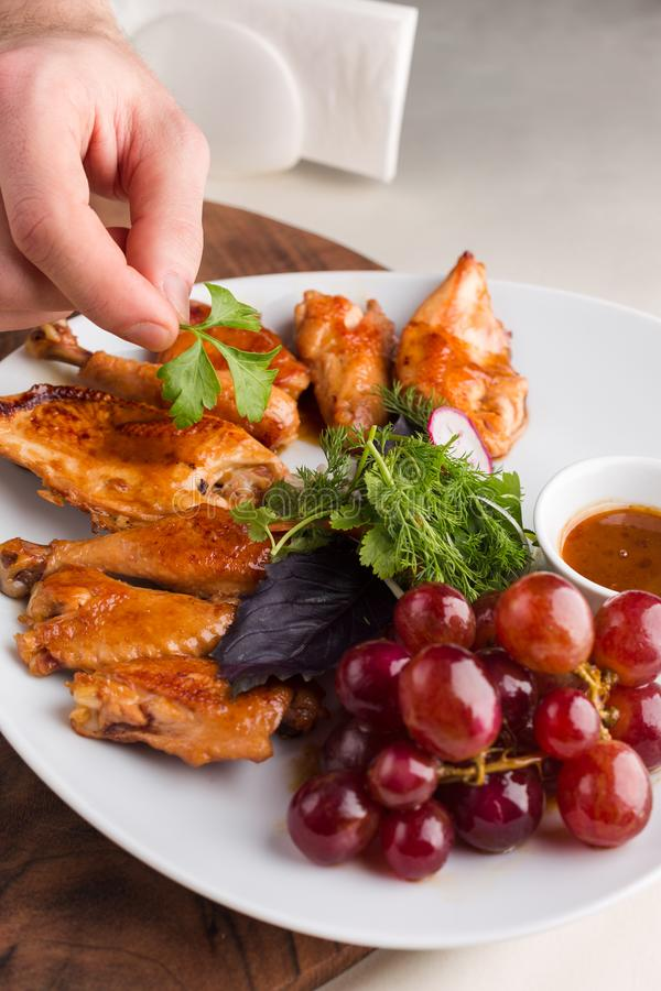 Chicken cooked in wine. On a white plate, served in restaurant. Chef making last preparation stock images
