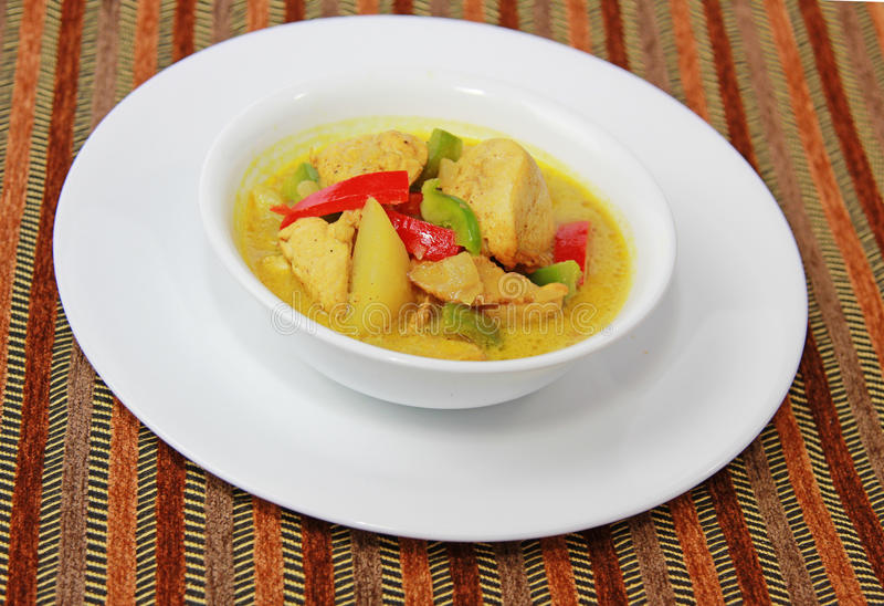 Chicken Curry. A bowl of chicken curry garnished with green and red peppers on a white dish set royalty free stock photography
