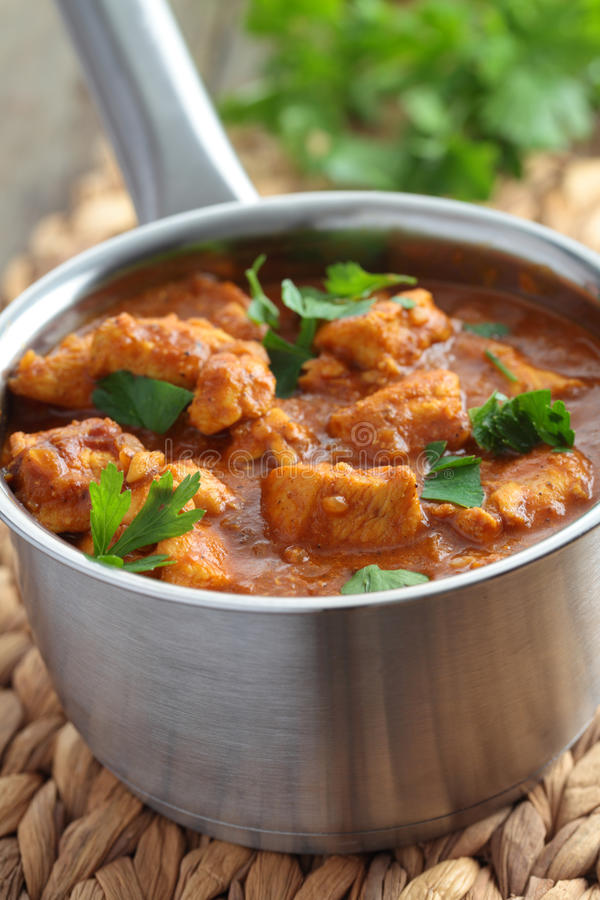 Chicken curry. With parsley in a saucepan royalty free stock images