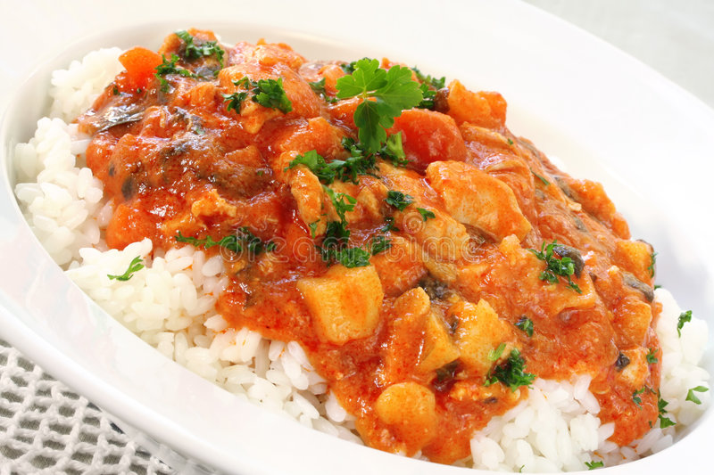 Chicken Curry. A bowl of chicken curry over steamed white rice stock photo