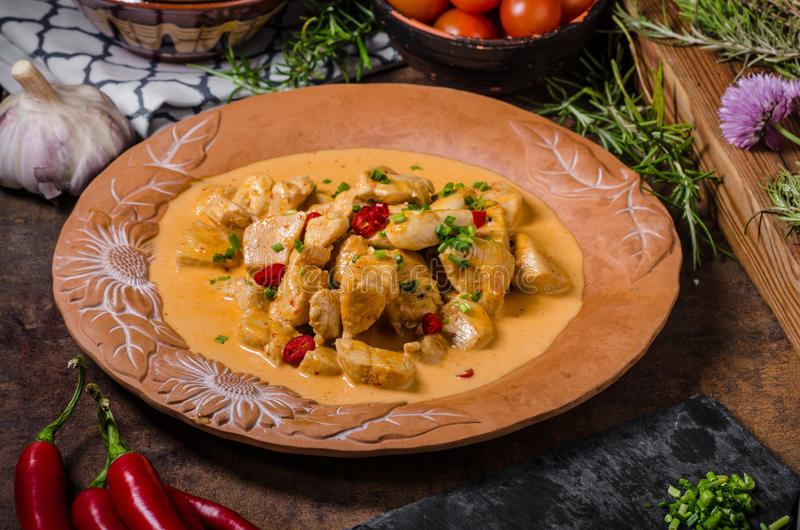 Chicken curry with herbs. Fresh chilli and herbs for delicious flavour, rustic plate royalty free stock photos