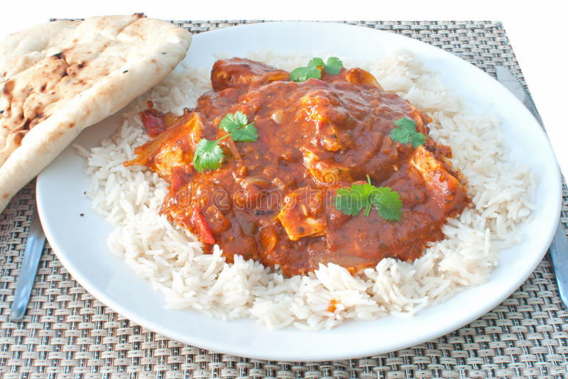Chicken curry. Plate of chicken curry with coriander and naan bread on the side royalty free stock image